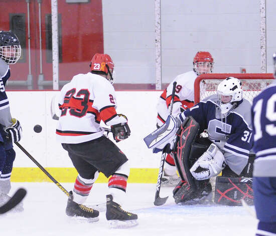 Matt Lodato # 23 of Greenwich at left, looks to play a loose puck as SWS goalie Matt Beckoff # 31 looks on during the boys high school ice hockey game between Staples-Weston-Shelton High School High School and Greenwich High School at Hamill Rink in Byram, Saturday night, Jan. 12, 2013. Photo: Bob Luckey / Greenwich Time