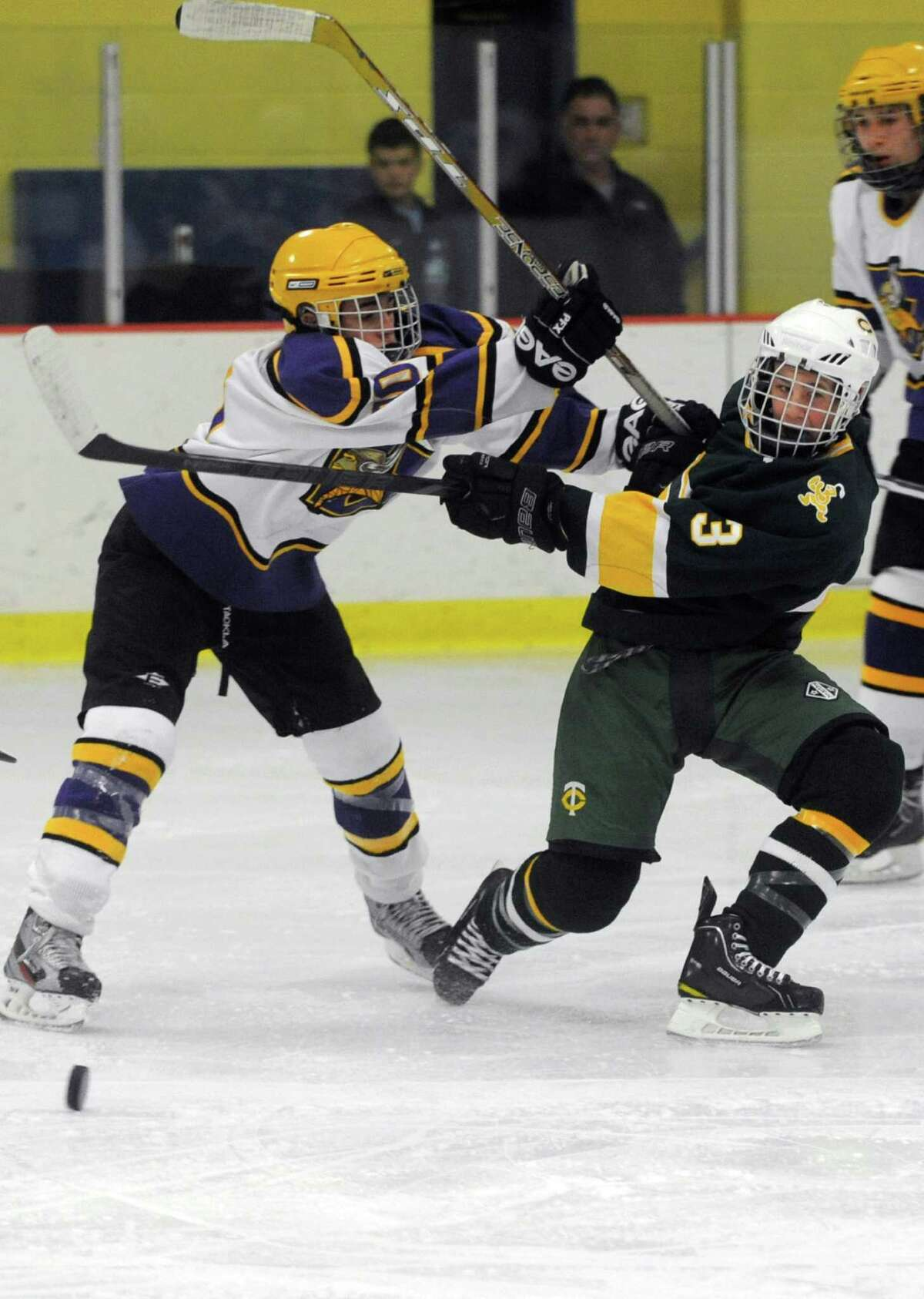 Westhill's Matthew Abt, left, and Trinity Catholic's Colin Bernard, right, compete for control of the puck during Saturday's boys ice hockey game at Terry Connors Rink in Stamford on January 12, 2013.