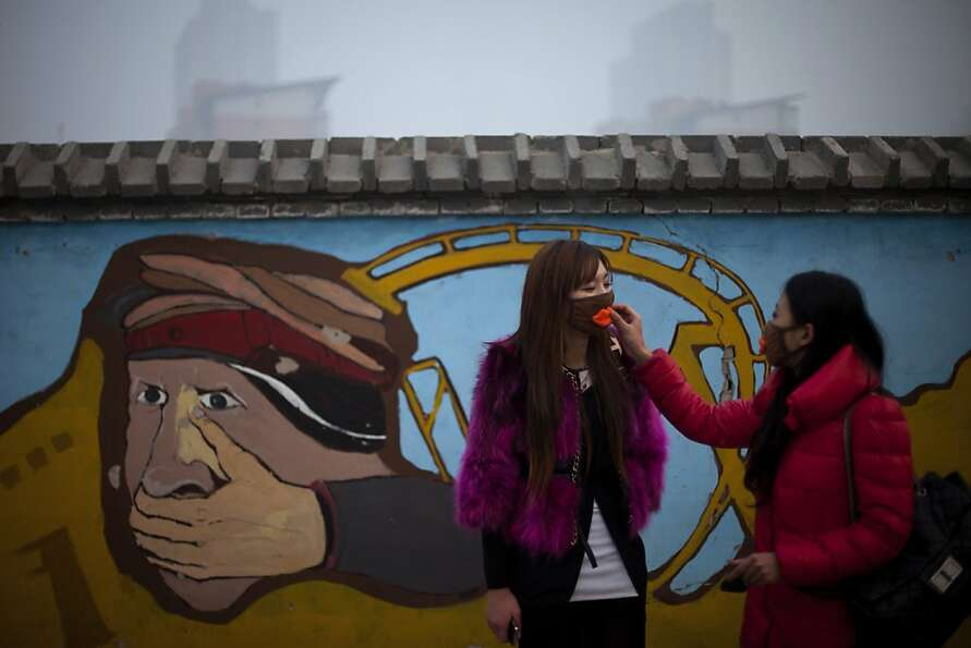 A woman helps adjust a mask for her friend outside an amusement park on a hazy day in Beijing Saturd