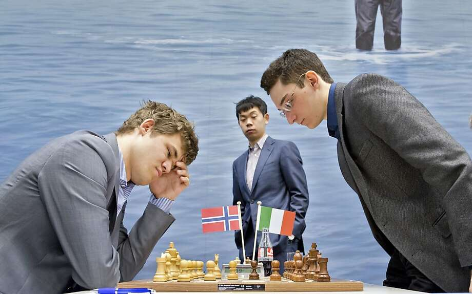 Chess players Magnus Carlsen (L) from Norway and Fabiano Caruana (R) from Italy compete during a game of chess at the Tata Steel Chess Tournament in Wijk aan Zee, the Netherlands, on January 12, 2013, as Chinese player Hao Wang looks on in the background. Photo: Koen Suyk, AFP/Getty Images