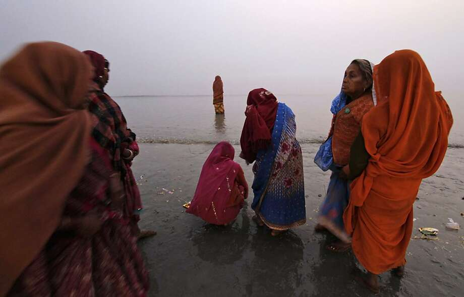 Indian women perform rituals on the beach at Gangasagar, India, Saturday, Jan. 12, 2013. The annual holy dip at Gangasagar, the confluence of Ganges River and Bay of Bengal, some 140 kilometers (87 miles) south of Kolkata, on the occasion of Makar Sankranti, is scheduled on Jan. 14. Photo: Bikas Das, Associated Press