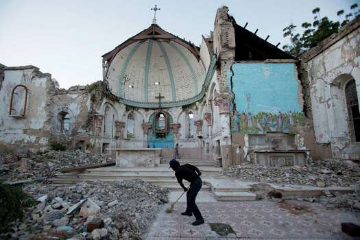 A man sweeps an exposed tiled area of the earthquake-damaged Santa Ana Catholic church, where he now lives, in Port-au-Prince, Haiti, Saturday, Jan. 12, 2013. Haitians recalled Saturday the tens of thousands of people who lost their lives in a devastating earthquake three years ago, marking the disaster's anniversary. Most of the rubble created by the quake has since been carted away but more than 350,000 people still live in displacement camps. (AP Photo/Dieu Nalio Chery) Photo: Dieu Nalio Chery