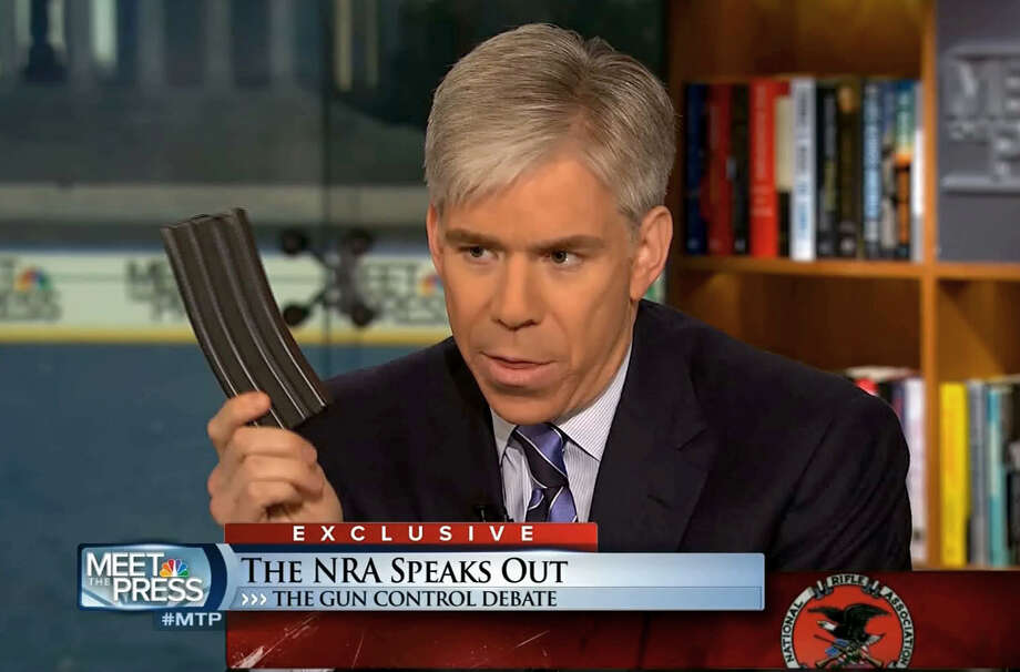 "This video frame grab image provided by""Meet the Press"" shows host David Gregory holding what he described as a high-capacity ammunition magazine during a recent Sunday's program.  Gregory won't face charges for displaying what he said was a high-capacity ammunition magazine on his ""Meet the Press"" show. D.C. prosecutors announced the decision Friday, saying criminal charges wouldn't serve the public's best interests.  (AP Photo/Meet the Press) Photo: Uncredited"