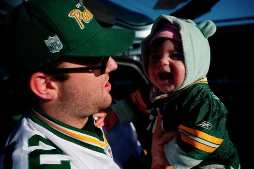 Landon Pikkel, of Palmdale, carries 7-months old daughter Jasmine in the parking lot outside Candlestick Park prior to a NFL football game between the San Francisco 49ers and Green Bay Packers in San Francisco, Calif. on Saturday, January 12, 2013. Photo: Stephen Lam, Special To The Chronicle / ONLINE_YES