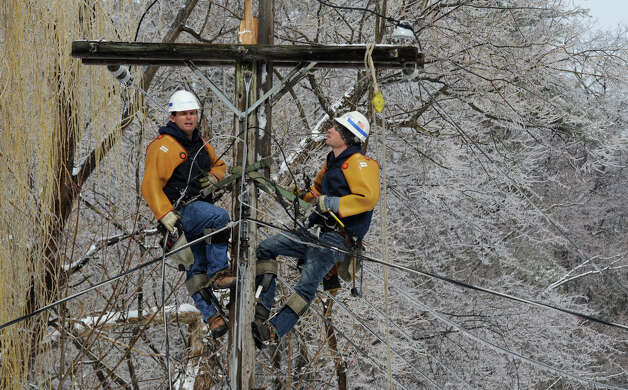 National Grid lineman Ron Carbinaro, left, and Shawn Demers, right, work on a power lines in the rear of 15 Wellington Road in Delmar, N.Y., which was damaged due to a late winter storm March 7, 2011. (Skip Dickstein / Times Union archive) Photo: Skip Dickstein / 2008