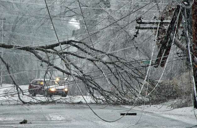 Traffic tries to find a way around downed trees and power lines on Hemlock Drive in the Clifton Knolls area of Clifton Park N.Y., Friday morning Dec. 12, 2008. (John Carl D'Annibale / Times Union archive) Photo: John Carl D'Annibale / 00001658B