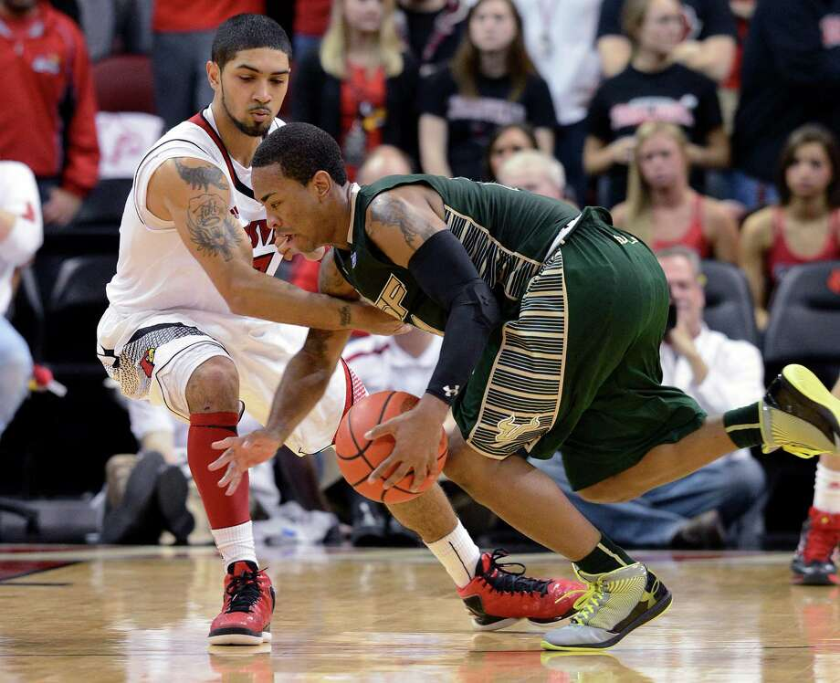 South Florida's Anthony Collins, right, attempts to keep the ball away from Louisville's Peyton Siva during the second half of an NCAA college basketball game Saturday, Jan. 12, 2013, in Louisville, Ky. Louisville defeated South Florida 64-38. (AP Photo/Timothy D. Easley) Photo: Timothy D. Easley