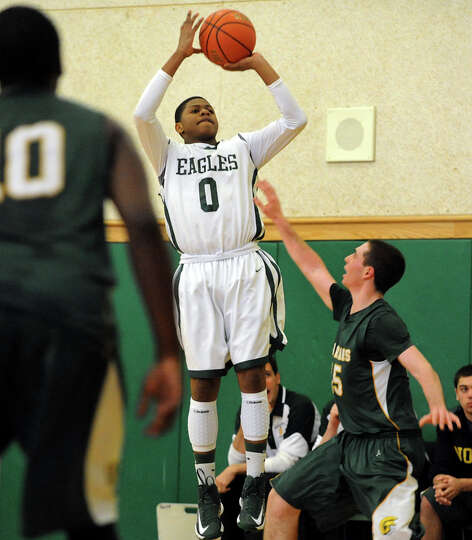 Green Tech's Najee Ward (0), center, shoots for the hoop as Williamsville North's David Birkun (15)