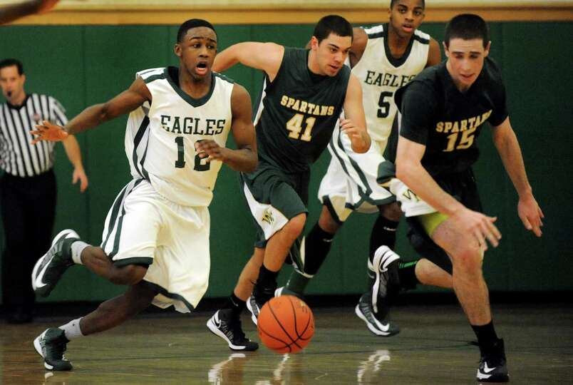 Green Tech's Jamil Hood Jr. (12), left, breaks away and drives up court during their basketball game