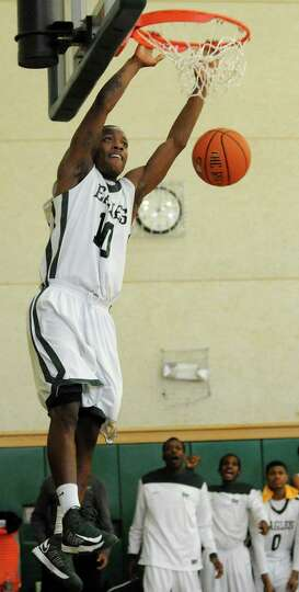 Green Tech's Maurice West (10) swings from the rim when he dunks the ball during their basketball ga
