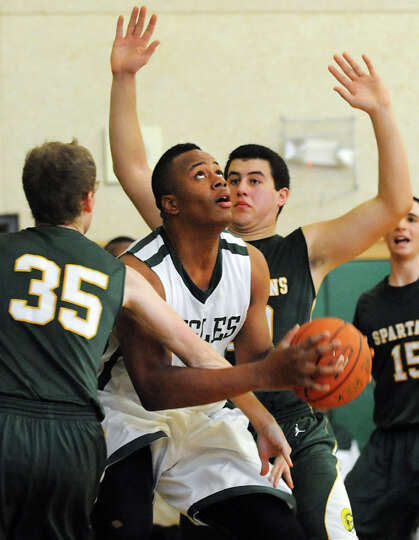 Green Tech's Kristopher Clark (1), center, looks to the hoop as Williamsville North's Casey Davis (3