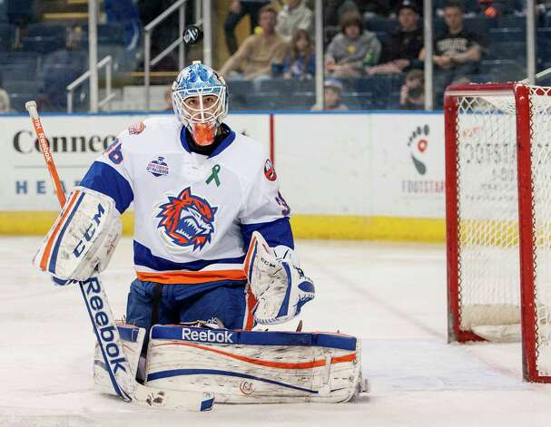 Bridgeport Sound Tigers goalie Kevin Poulin watches the puck fly over his head after he deflected a shot on goal during an American Hockey League game against the Portland Pirates played at the Webster Bank Arena, Bridgeport, CT on Saturday January 12th, 2013. Photo: Mark Conrad / Connecticut Post Freelance