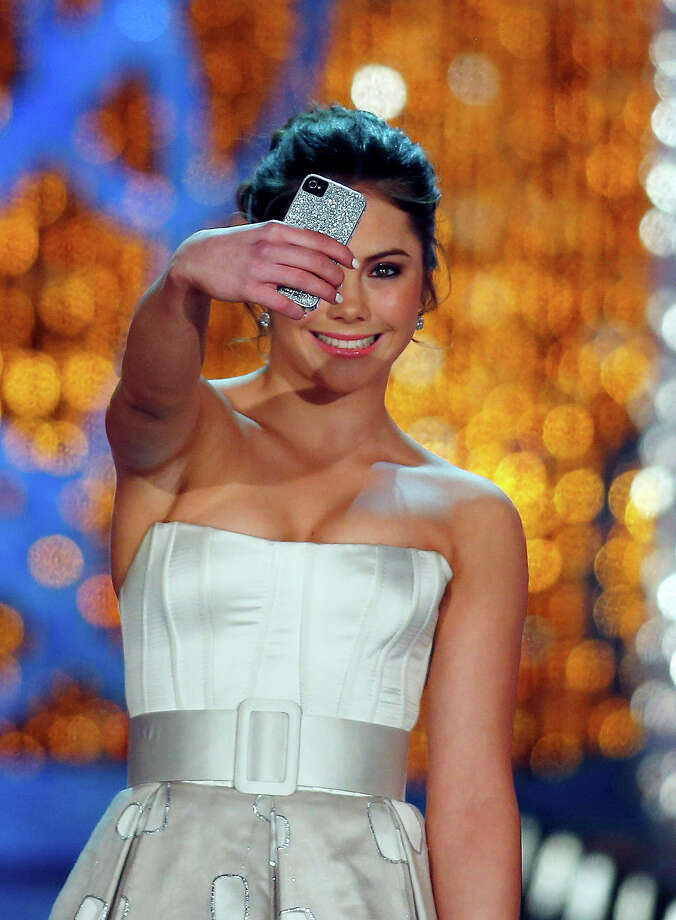 Miss America judge McKayla Maroney photographs herself onstage before the pageant on Saturday, Jan. 12, 2013, in Las Vegas. (AP Photo/Isaac Brekken) Photo: Isaac Brekken, ASSOCIATED PRESS / AP2013