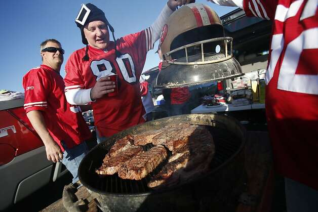 Chris McAllister, of San Mateo, opens a grill full of steak in the parking lot outside Candlestick Park prior to a NFL football game between the San Francisco 49ers and Green Bay Packers in San Francisco, Calif. Saturday, January 12, 2013. Photo: Stephen Lam, Special To The Chronicle