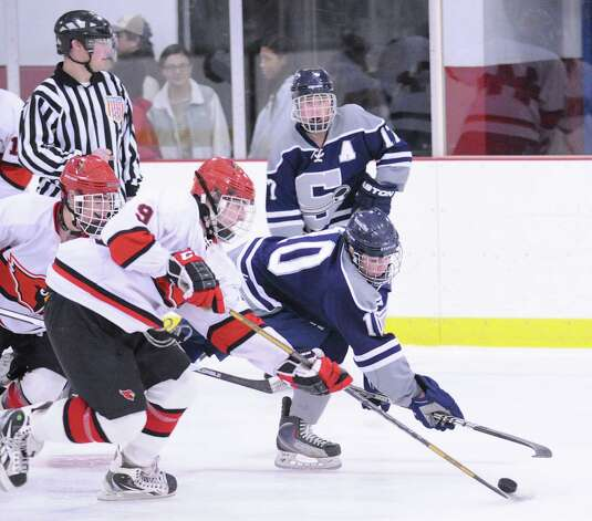 Alex Bastone # 9 of Greenwich stick-checks the puck away from SWS player Thomas Meyers # 10 during the boys high school ice hockey game between Staples-Weston-Shelton High SchoolHigh School and Greenwich High School at Hamill Rink in Byram, Saturday night, Jan. 12, 2013. Photo: Bob Luckey / Greenwich Time