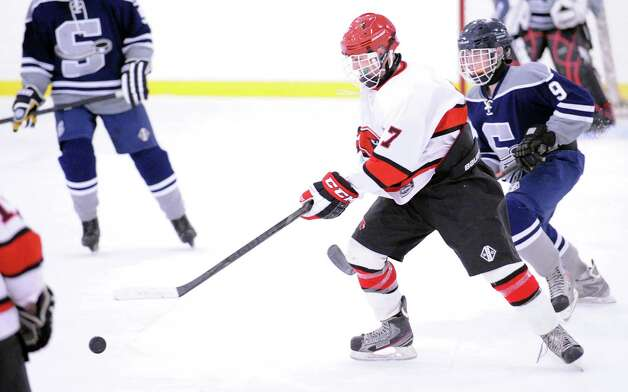 At center, Brian Silard # 7 of Greenwich advances the puck as Derek Nussbaum # 9 of SWS pursues during the boys high school ice hockey game between Staples-Weston-Shelton High School High School and Greenwich High School at Hamill Rink in Byram, Saturday night, Jan. 12, 2013. Photo: Bob Luckey / Greenwich Time