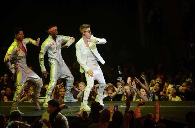 "Justin Bieber, right, and dancers perform at the AT&T Center on a stop of the ""Believe"" tour on Saturday night, Jan. 12, 2013. Photo: Billy Calzada, San Antonio Express-News / SAN ANTONIO EXPRESS-NEWS"