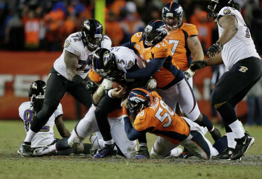 Baltimore Ravens quarterback Joe Flacco (5) is sacked by Denver Broncos defensive end Elvis Dumervil (92) and outside linebacker Von Miller (58) in overtime of an AFC divisional playoff NFL football game, Saturday, Jan. 12, 2013, in Denver. (AP Photo/Joe Mahoney) Photo: Joe Mahoney, Associated Press / FR170458 AP