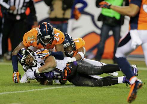 Baltimore Ravens running back Ray Rice (27) is tackled by Denver Broncos cornerback Champ Bailey (24) and Denver Broncos free safety Rahim Moore (26) for a first down in the third quarter of an AFC divisional playoff NFL football game, Saturday, Jan. 12, 2013, in Denver. (AP Photo/Charlie Riedel) Photo: Charlie Riedel, Associated Press / AP