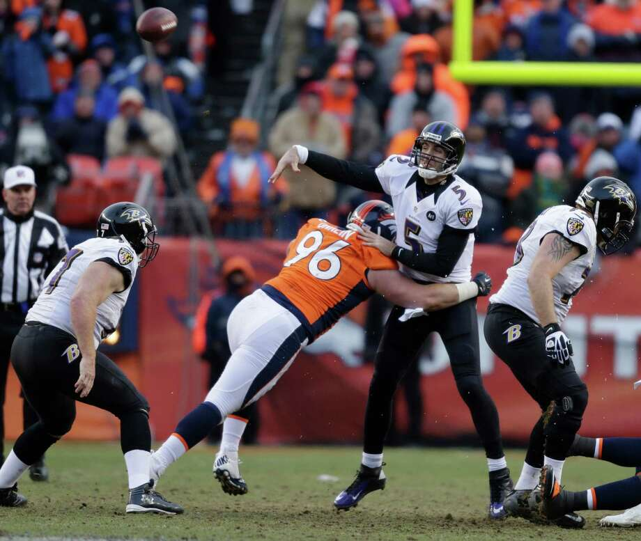 Baltimore Ravens quarterback Joe Flacco (5) is hit as he throws by Denver Broncos defensive tackle Mitch Unrein (96) in the third quarter of an AFC divisional playoff NFL football game, Saturday, Jan. 12, 2013, in Denver. (AP Photo/Joe Mahoney) Photo: Joe Mahoney, Associated Press / FR170458 AP