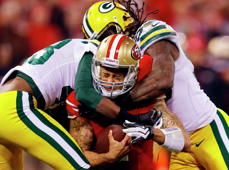 San Francisco 49ers quarterback Colin Kaepernick (7) is tackled by Green Bay Packers free safety M.D. Jennings (43) and outside linebacker Erik Walden (93) during the second quarter of an NFC divisional playoff NFL football game in San Francisco, Saturday, Jan. 12, 2013. Photo: Marcio Jose Sanchez, Associated Press / AP