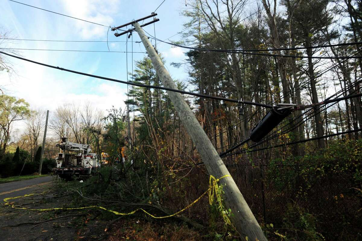 Crews from Connecticut Light & Power, AT&T and a tree crew from North Carolina work to clear a road near Stamford, Conn.