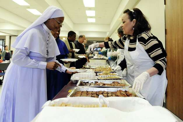Morline Guillory, right, serves Sister Faustina of the Daughters of Mary Mother of Mercy during the reception after the celebration of the Message of Dr. Martin Luther King, Jr.  on Saturday, January 12, 2013, at Saint Anthony Cathedral Basilica in Beaumont.  Photo taken: Randy Edwards/The Enterprise Photo: Randy Edwards