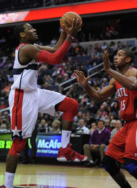 Wizards point guard John Wall (2) drives on the Hawks' Al Horford in the fourth quarter of Washington's 93-83 victory Saturday. Wall had 14 points and four assists in his first game of the season after returning from knee surgery. Photo: CHUCK MYERS / MCT