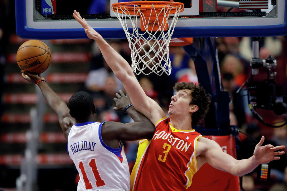 Jrue Holiday, left, goes up for a shot against Omer Asik. Photo: Matt Slocum, Associated Press / AP