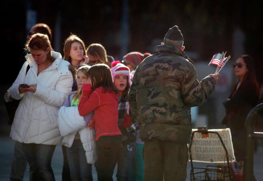 A group of children and other pedestrians watch as disabled Vet Philip Myers holds a bouquet of American flags in front of the Ferry Plaza. Photo: Mike Kepka, The Chronicle / ONLINE_YES