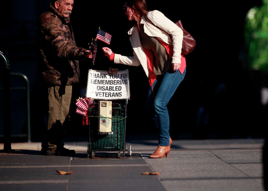 A women takes a flag for her donation from disabled Vet Philip Myers in front of the Ferry Building. Photo: Mike Kepka, The Chronicle / ONLINE_YES