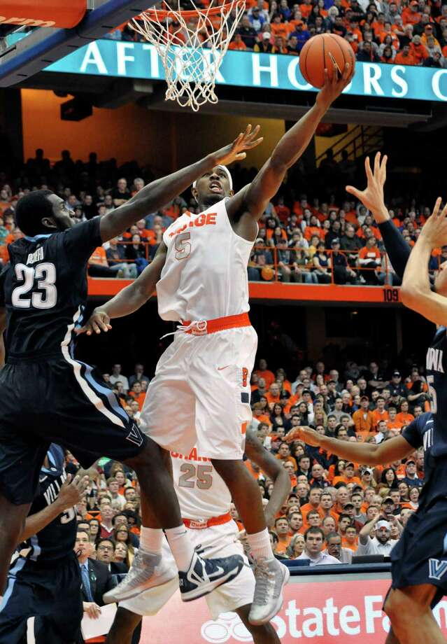 Syracuse's C. J. Fair scores against Villanova's Daniel Ochefu,left, during the second half of an NCAA college basketball game in Syracuse, N.Y., Saturday, Jan. 12, 2013. Syracuse won 72-61. (AP Photo/Kevin Rivoli) Photo: KEVIN RIVOLI