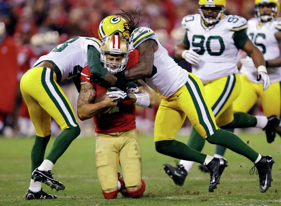 San Francisco 49ers quarterback Colin Kaepernick (7) is tackled by Green Bay Packers free safety M.D. Jennings (43) and outside linebacker Erik Walden (93) during the second quarter of an NFC divisional playoff NFL football game in San Francisco, Saturday, Jan. 12, 2013. (AP Photo/Marcio Jose Sanchez) Photo: Marcio Jose Sanchez, Associated Press / AP
