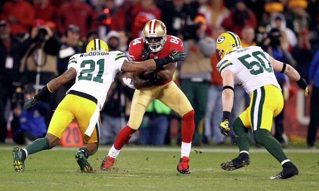 San Francisco 49ers wide receiver Randy Moss (84) is tackled by Green Bay Packers strong safety Charles Woodson (21) and inside linebacker A.J. Hawk (50) during the first quarter of an NFC divisional playoff NFL football game in San Francisco, Saturday, Jan. 12, 2013. (AP Photo/Tony Avelar) Photo: Tony Avelar, Associated Press / FR155217 AP