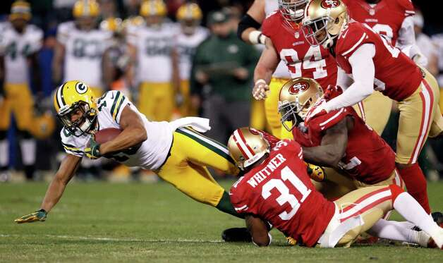 Green Bay Packers wide receiver Randall Cobb (18) is tackled by San Francisco 49ers safety Donte Whitner (31), linebacker Patrick Willis (52), and defensive back Perrish Cox (20) during the third quarter of an NFC divisional playoff NFL football game in San Francisco, Saturday, Jan. 12, 2013. (AP Photo/Tony Avelar) Photo: Tony Avelar, Associated Press / FR155217 AP