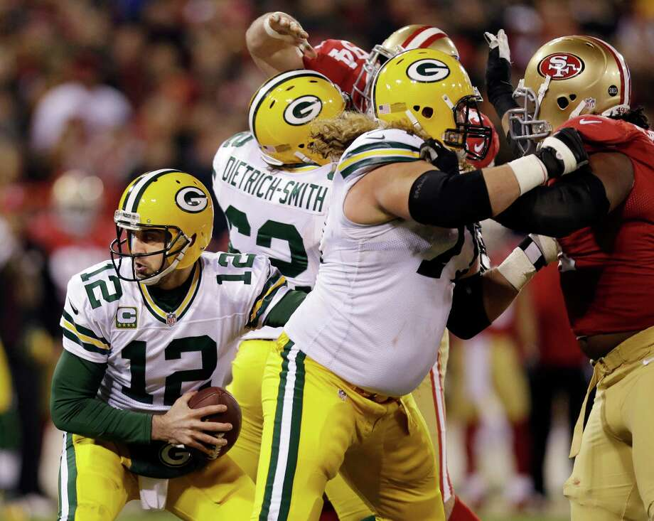 Green Bay Packers quarterback Aaron Rodgers (12) drops back behind the his defenders against the San Francisco 49ers during the second quarter of an NFC divisional playoff NFL football game in San Francisco, Saturday, Jan. 12, 2013. (AP Photo/Marcio Jose Sanchez) Photo: Marcio Jose Sanchez, Associated Press / AP