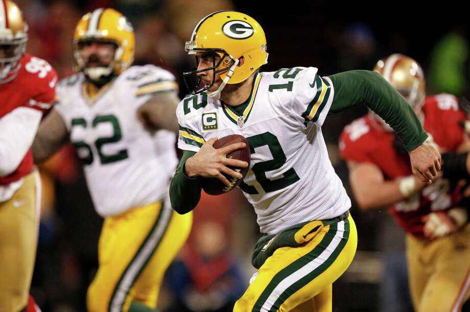 Green Bay Packers quarterback Aaron Rodgers (12) scrambles against the San Francisco 49ers during the second half of an NFC divisional playoff NFL football game in San Francisco, Saturday, Jan. 12, 2013. (AP Photo/Tony Avelar) Photo: Tony Avelar, Associated Press / FR155217 AP