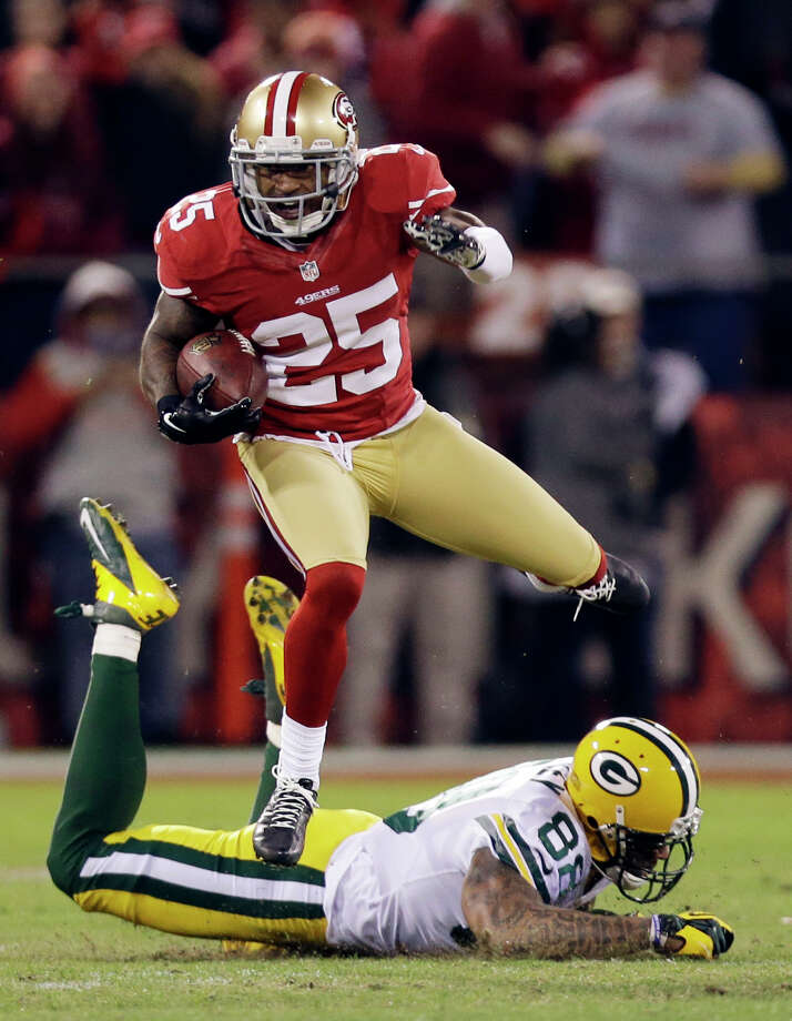 San Francisco 49ers cornerback Tarell Brown (25) returns an interception from Green Bay Packers quarterback Aaron Rodgers as he leaps over Green Bay Packers tight end Jermichael Finley (88) in the first half of an NFC divisional playoff NFL football game in San Francisco, Saturday, Jan. 12, 2013. (AP Photo/Marcio Jose Sanchez) Photo: Marcio Jose Sanchez, Associated Press / AP