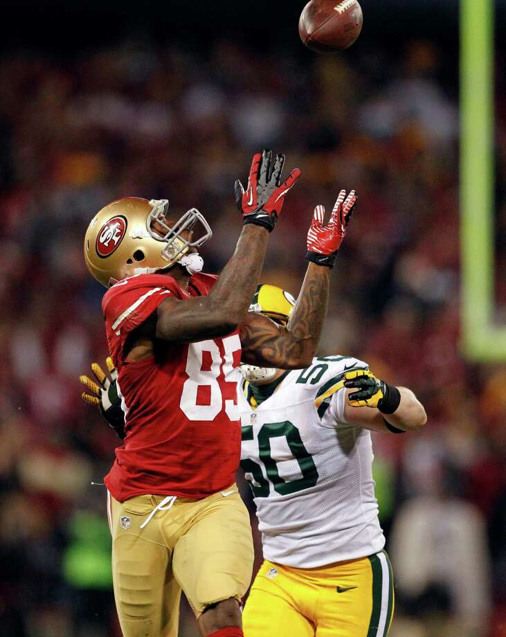 San Francisco 49ers tight end Vernon Davis (85) catches a pass over Green Bay Packers inside linebacker A.J. Hawk (50) during the third quarter of an NFC divisional playoff NFL football game in San Francisco, Saturday, Jan. 12, 2013. (AP Photo/Tony Avelar) Photo: Tony Avelar, Associated Press / FR155217 AP
