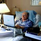Gene Patterson, former chairman and chief executive of the Times Publishing Company and its affiliates, checks his email from his bed in St. Petersburg, Fla, in August. Patterson edited 600,000 words out of the King James Bible shown at right, sitting on top of his finished manuscript. Newspaper editor and columnist Eugene Patterson, who helped fellow Southern whites understand the civil rights movement. He died Saturday at 89.  (AP Photo/The Tampa Bay Times, Cherie Diez)