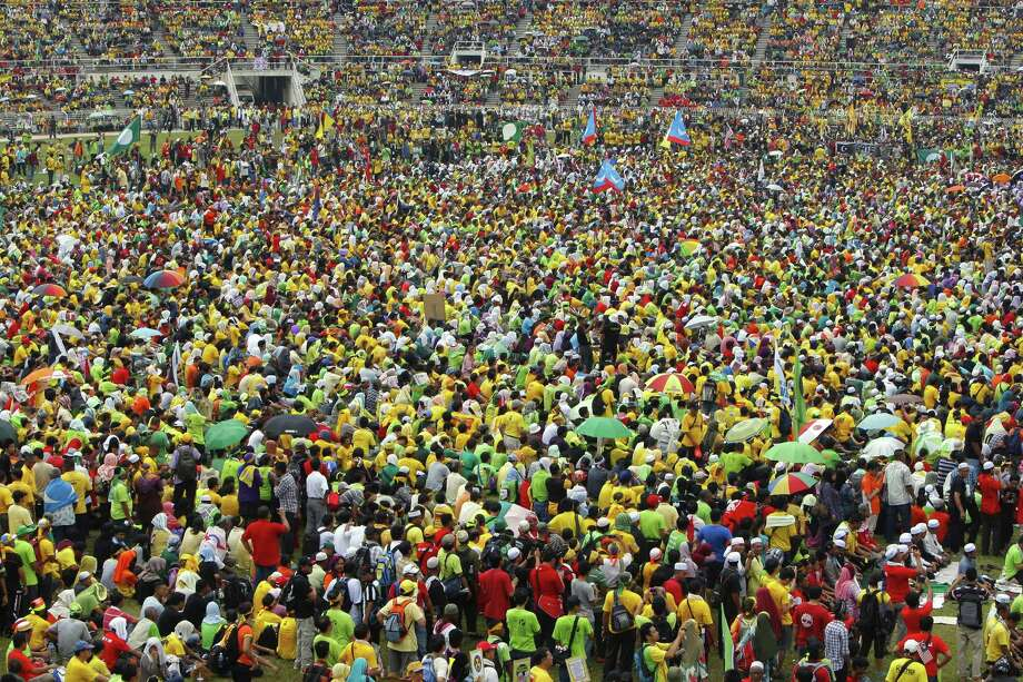 Malaysian protesters listen to their leader's speech during the People's Uprising Rally at Merdeka Stadium in Kuala Lumpur, Malaysia, on Saturday. More than 45,000 Malaysians have joined the massive opposition rally in a show of force ahead of general elections due in months. Photo: AP