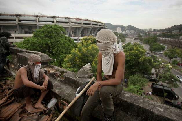 Two masked men keep a lookout on the rooftop an old Indian museum, in Rio de Janeiro, Brazil, Saturday, Jan. 12, 2013. Police in riot gear on Saturday surrounded the site in preparation for the eviction of  an indigenous settlement of men and women living on the grounds of the old museum . The settlement is next to the Maracana stadium, pictured left in background, which is being refurbished to host the opening and closing ceremonies of the 2016 Olympics and the final match of the 2014 World Cup. Authorities say the compound must go as the area around the stadium is also being refurbished, expected to be transformed into a shopping and sports entertainment hub. Photo: AP