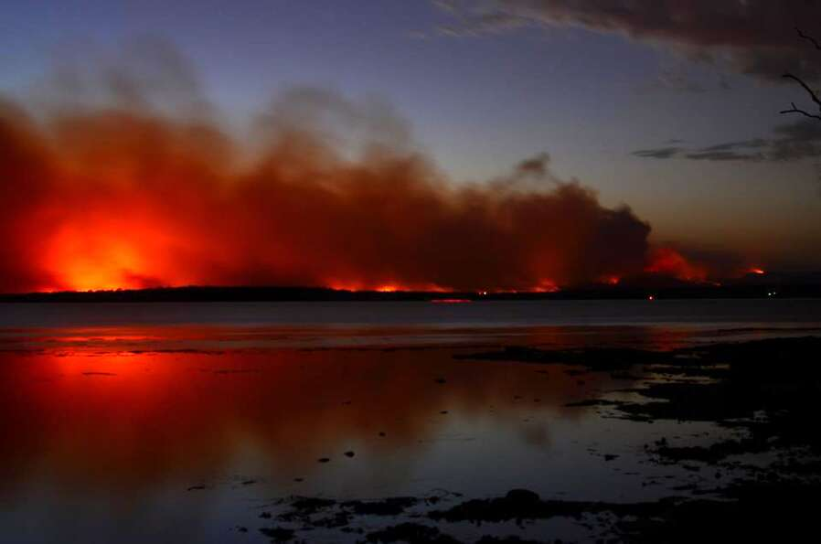 A fire burns near Sussex Inlet, Australia, on Saturday. Firefighters are battling scores of wildfire