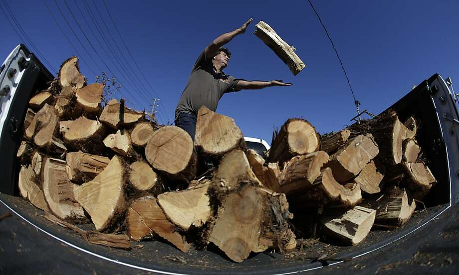 Jacinto Torres stacks logs in the back of a pick-up truck at The Woodshed, a firewood lot in Orange, Calif. Friday, Jan. 11, 2013. California remained in the grip of a cold snap that's expected to last through the weekend.  Photo: Chris Carlson, Associated Press