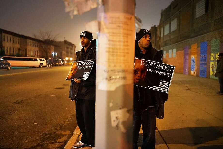 Members of Save Our Streets (S.O.S.) hold a rally and vigil on the sidewalk near where a 16-year-old boy was shot last Tuesday evening, on January 12, 2013 in the Crown Heights neighborhood of the Brooklyn borough of New York City. The gathering was sponsored by the local group S.O.S., which is a community-based effort to end gun violence. S.O.S. holds the gatherings at all shooting locations in Crown Heights to draw attention to the violence and to encourage a community response to the shootings. While murders were down for 2012 in New York City, gun violence continues to plague many communities.  Photo: Spencer Platt, Getty Images