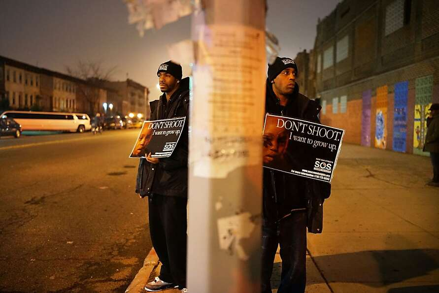 Members of Save Our Streets (S.O.S.) hold a rally and vigil on the sidewalk near where a 16-year-old