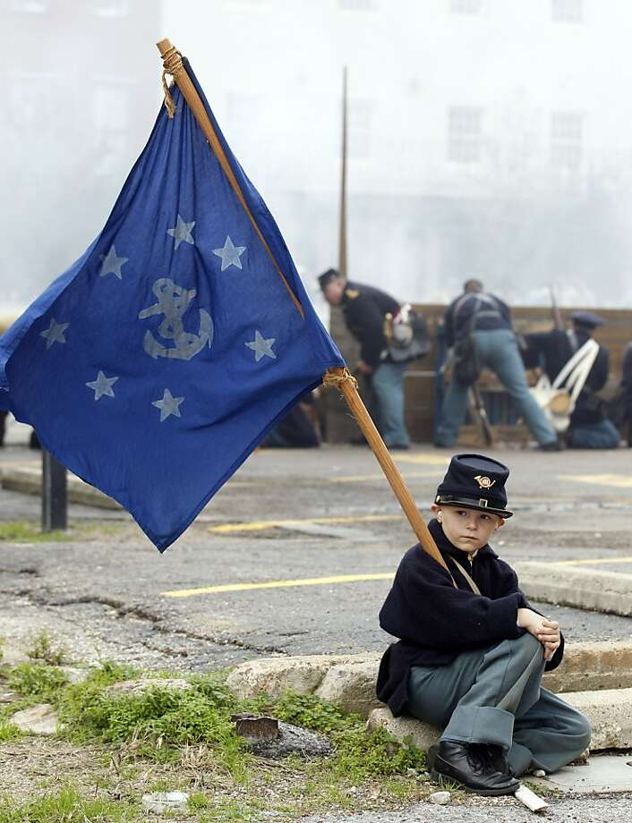 Eight-year-old Daniel Martin holds a Naval Jack as a firefight at Kuhn's Wharf rages behind him during a reenactment of the Civil War Battle of Galveston, Texas on Saturday afternoon January 12, 2013 on The Strand. The Galveston Historical Foundation marked the 150th anniversary with re-enactments, lectures, living history encampments and a other events focusing on Galveston's part in the 1863 battle.  Photo: Kevin M. Cox, Associated Press