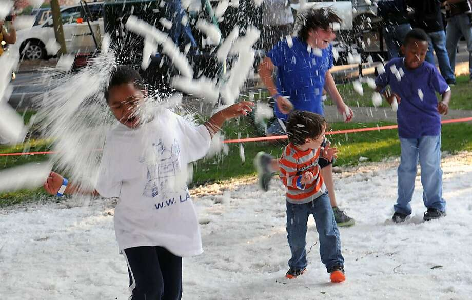"A young boy is hit as freshly shaved ice is sprayed during the ""Blizzard at Ardsley Park"" Saturday, Jan. 12. 2013 at Tiedeman Park in Savannah, Ga. Photo: Richard Burkhart, Associated Press"