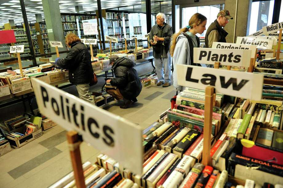 Book lovers peruse titles for sale during the annual Winter Non-Fiction Used Book Sale on Saturday, Jan. 12, 2013, at the Schenectady County Public Library in Schenectady, N.Y. The sale, sponsored by the Friends of SCPL, continues Sunday from 1 to 5 p.m. and Monday from 9 a.m. to 5 p.m. (Cindy Schultz / Times Union) Photo: Cindy Schultz / 00020640A
