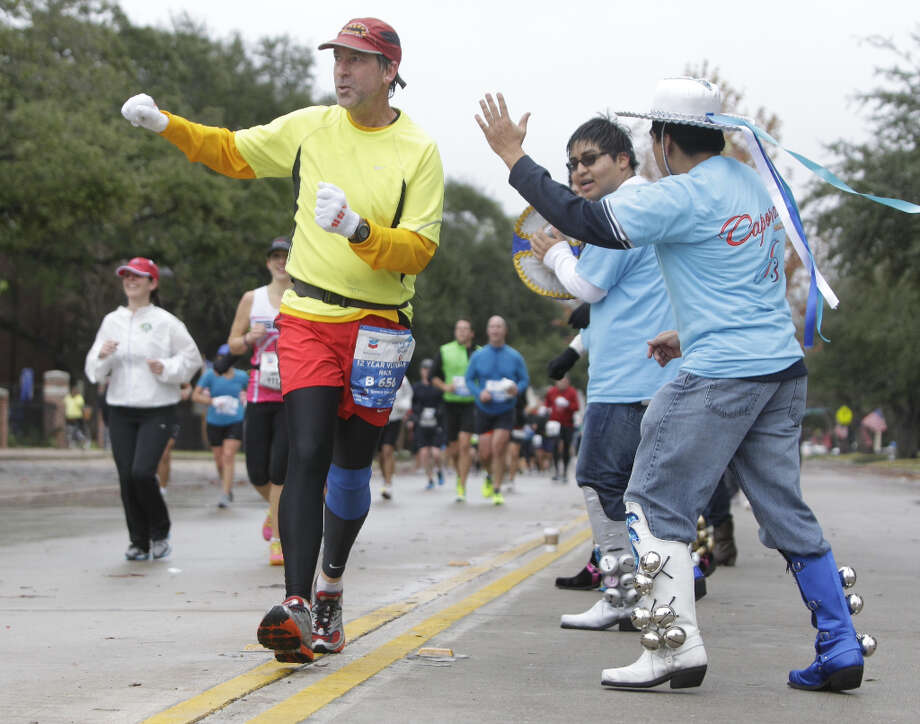 A runner dances with Bolivian dance group along University near mile 13 of the Chevron Houston Marathon.